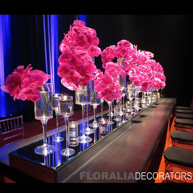 Tall stemmed candle holder vases with fuchsia orchids on long rectangle table