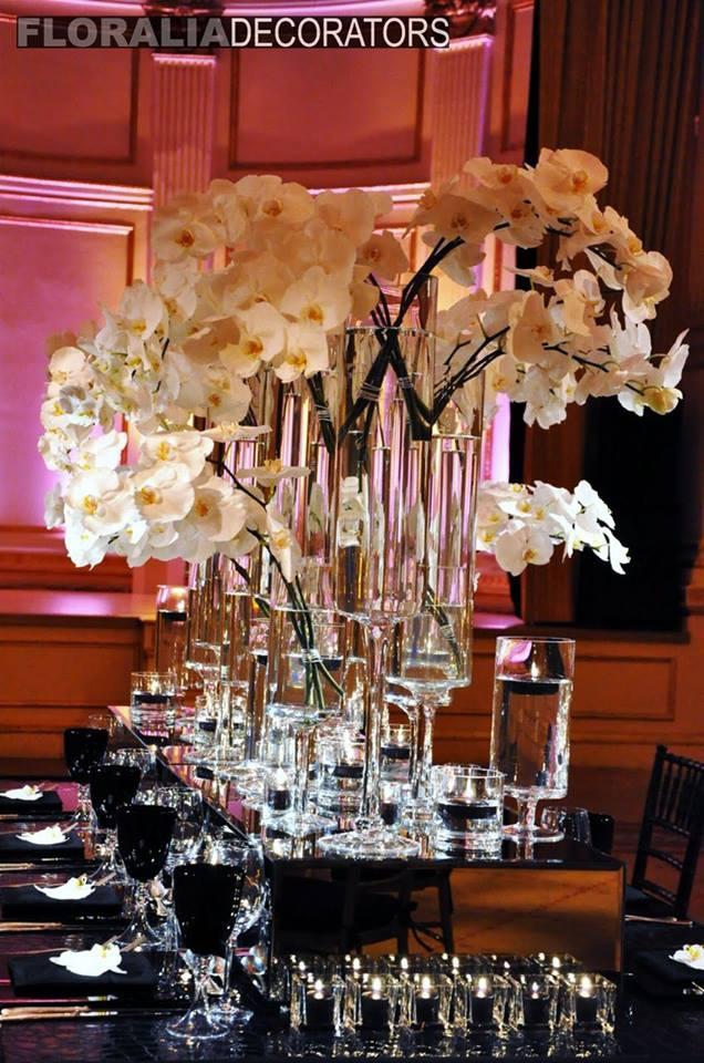 tall stemmed candle holder vases with white orchids centerpiece on long rectangular table